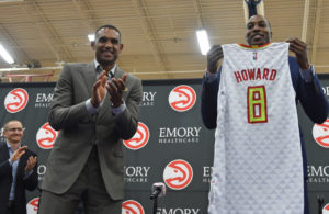 Dwight Howard holds the jersey presented to him by Grant Hill, left, during a news conference introducing Howard as the newest member of the Atlanta Hawks Wednesday July 13, 2016, in Atlanta.  (Brandt Sanderlin/Atlanta Journal-Constitution via AP)   ORG XMIT: GAATJ204